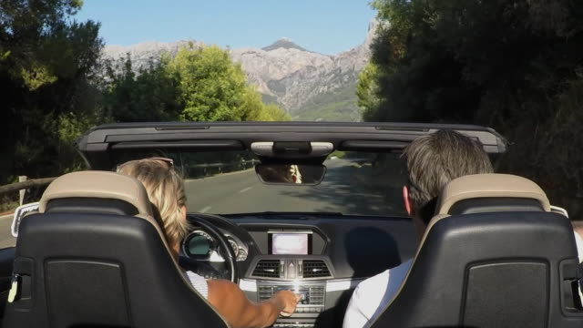 Couple in convertible car driving on country road