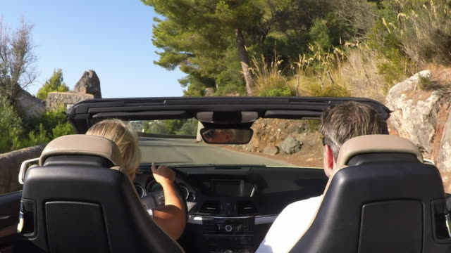 Couple in convertible car driving on country road Spain, Mallorca. luxury car stock videos & royalty-free footage
