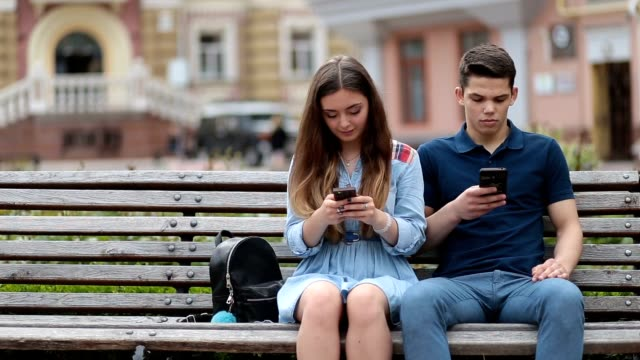 Couple in disinterest moment with phones outdoors Hipster couple sitting on the bench in park, browsing in smartphones and showing mutual disinterest. Concept of relationship apathy, usage of new technology and mobile phone addiction. ignoring stock videos & royalty-free footage