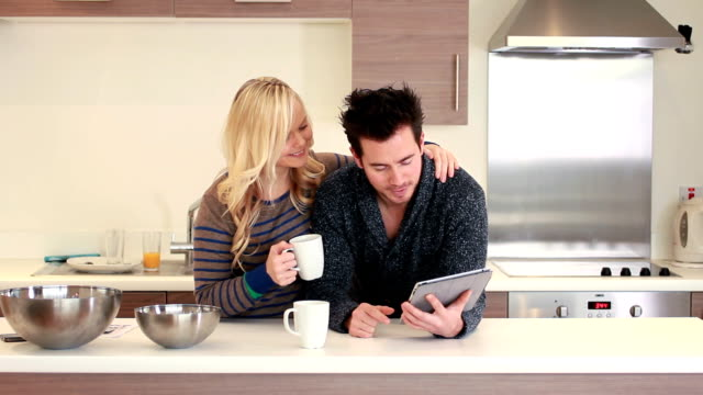 couple in kitchen looking at digital tablet video