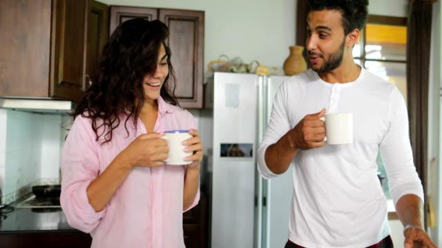 Couple dans la cuisine, homme et femme boire un café tenant les cuvettes avec ordinateur portable parler jeune famille Communication - Vidéo