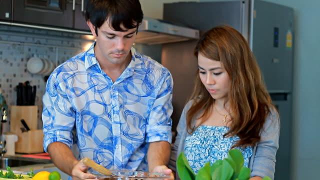 couple in kitchen together prepare meal - 30 39 år bildbanksvideor och videomaterial från bakom kulisserna
