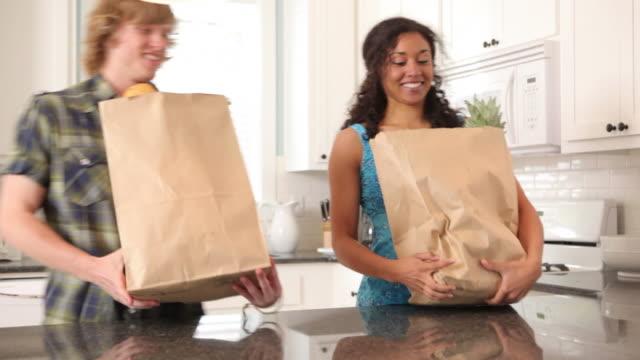 Couple in kitchen with grocery bags video