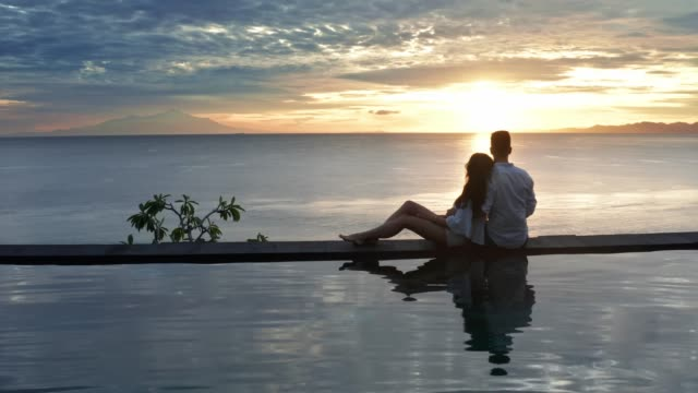 couple in love at luxury resort on romantic summer vacation. people relaxing together in edge swimming pool , enjoying beautiful sunset sea view. happy lovers on honeymoon travel. relationship, romance. aerial shot 4k - affluent lifestyles stock videos & royalty-free footage