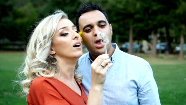 couple in love blowing dandelion