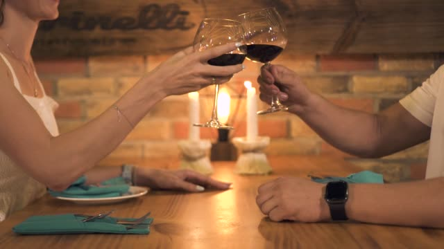 Couple in love clink wineglasses and drinking red wine at romantic dinner with candles in restaurant. Man and woman drinking red wine from glasses at date in romantic restaurant Couple in love clink wineglasses and drinking red wine at romantic dinner with candles in restaurant. Man and woman drinking red wine from glasses at date in romantic restaurant valentines day stock videos & royalty-free footage