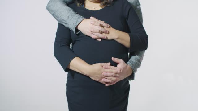 vidéos et rushes de couple dans le concept de l'amour homme femme embrassant tenant par la main tenant le frottement ventre corps angle grossesse - fête de naissance
