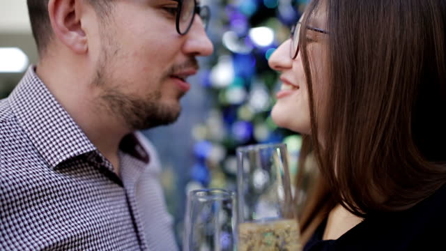 Couple in love drinking champagne, make a wish and kiss the Christmas decorations. Kiss on the background of the Christmas tree.