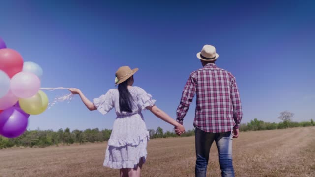 Couple in love hand holding colorful balloons and walking outdoors a summer day at the field