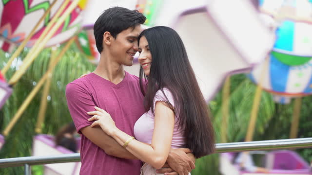 couple in love hugging and kissing together at the amusement park outdoors in summer having fun in vacation