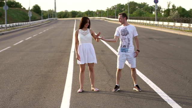A couple in love is having fun dancing on an empty track. Slow motion.