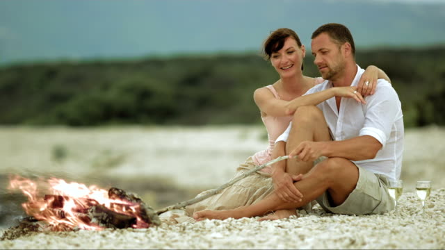 SLO MO Couple in love on beach by the fire video
