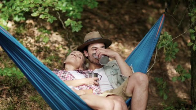 couple in love relaxing on hammock in forest - amaca video stock e b–roll