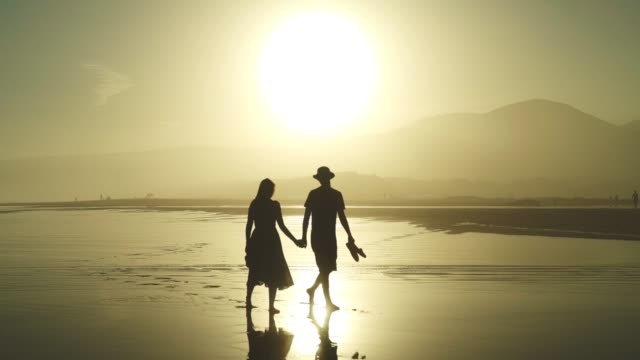 Couple in love walking on a hot day on the beach at sunset