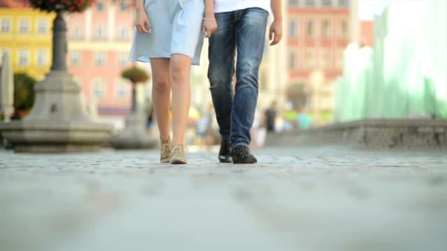 çift aşk yürüyüş midday.the hava, kaldırımda sunny ve ısı olduğunu. bir çift eğlenmek - uzun adımlarla yürümek stok videoları ve detay görüntü çekimi