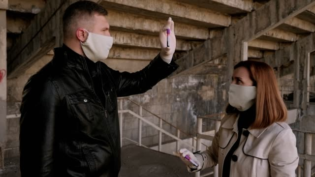 Couple in medical masks and gloves hold a blood sample of the new COVID-19 virus