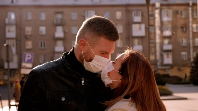 Couple in medical masks standing embracing on a street in the city. Covid-19. Close-up of a couple in love in medical masks standing embracing on a street in the city. Concept of a new coronavirus and quarantine. COVID-19. kissing stock videos & royalty-free footage