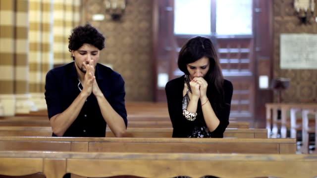 couple in prayer in a church video