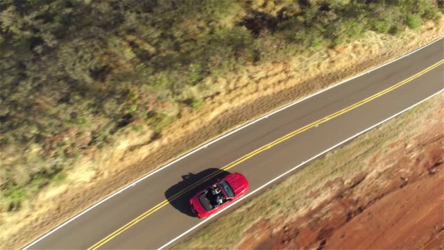 AERIAL CLOSE UP: Couple in red convertible car driving along countryside road