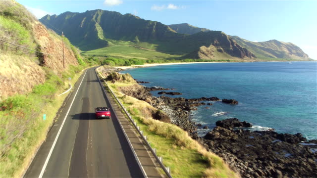 AERIAL: Couple in red convertible car driving along Hawaiian coastal road video