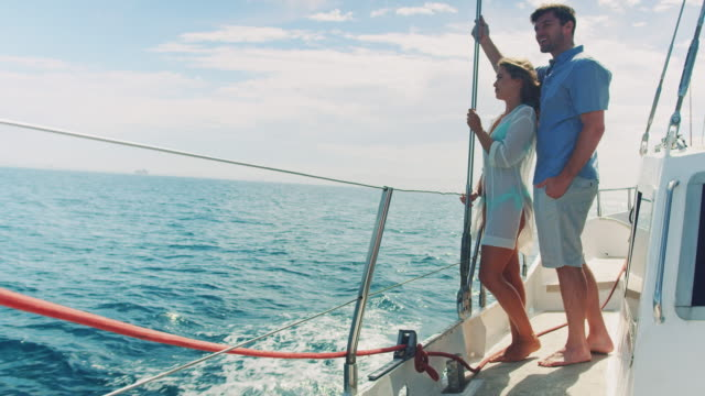 Couple in sailing boat A young couple standing on a sailing boat. They enjoying the summerday and looking over the ocean. yacht stock videos & royalty-free footage