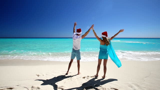 Couple in Santa Claus hats jumping on tropical sandy beach video