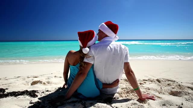 カップルのサンタクロース帽子座って熱帯の砂のビーチ - サンタの帽子点の映像素材/bロール
