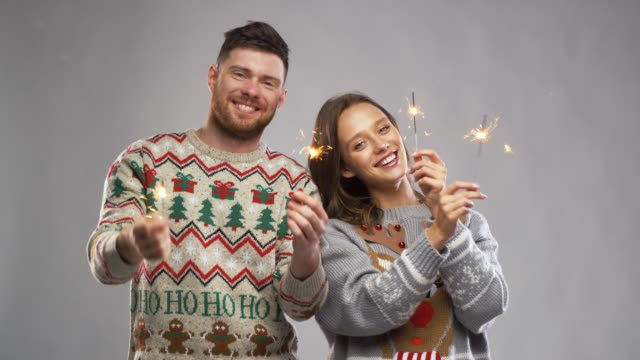 couple in ugly sweaters with sparklers at christmas party