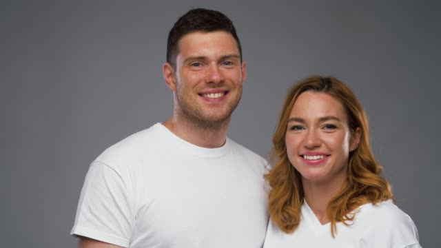 couple in white t-shirts over grey background - maglietta bianca video stock e b–roll