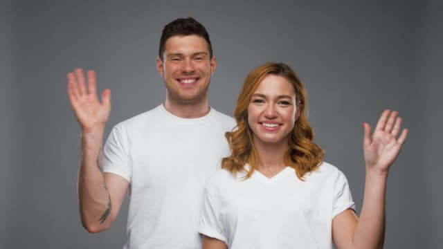 couple in white t-shirts waving hands gesture and people concept - happy smiling couple in white t-shirts waving hands over grey background boyfriend stock videos & royalty-free footage