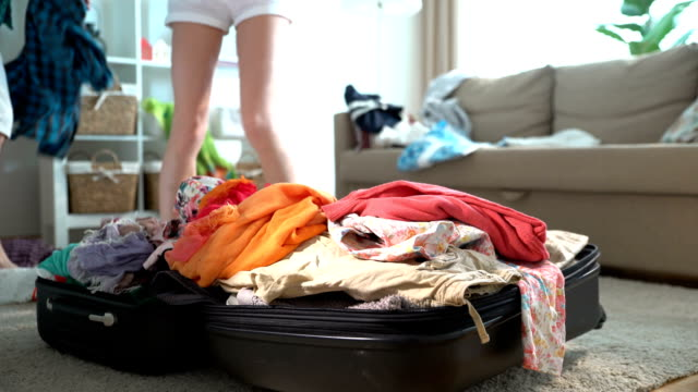 A couple is haphazardly packing and trying to close a chock-full suitcase. Time lapse video