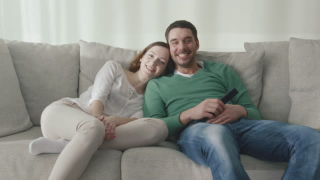 Couple is sitting on the couch at home and watching tv. video