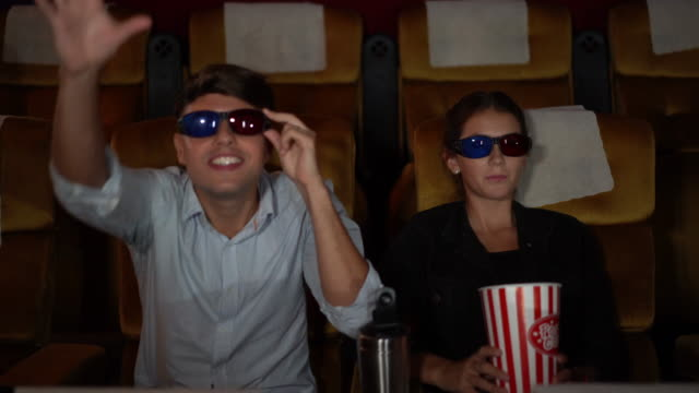 Couple is sitting watching a 3D movie