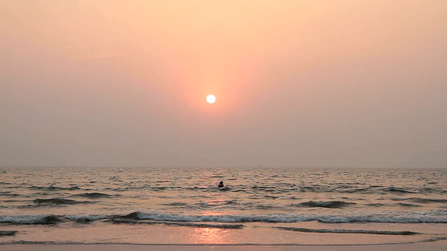 couple is swimming in the ocean at sunset video
