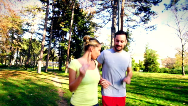 Couple jogging in park on sunny day. video