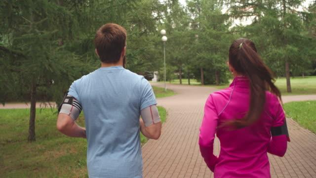 par jogging i park - strumpbyxor bildbanksvideor och videomaterial från bakom kulisserna