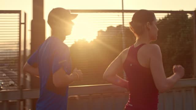 slo mies. ts para jogging w miasta o zachodzie słońca - 30 39 lat filmów i materiałów b-roll