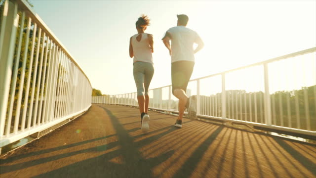 vídeos de stock e filmes b-roll de couple jogging outdoors. - young woman running city