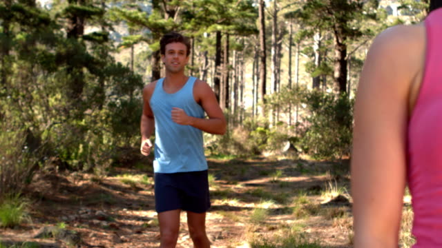 Couple jogging through a forest Couple jogging through a forest in slow motion arms akimbo stock videos & royalty-free footage