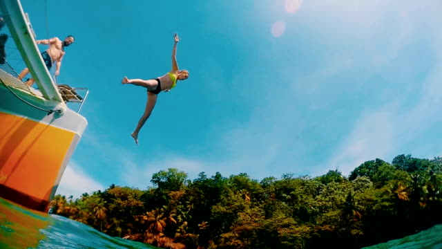 couple jumping into turquoise water. holiday enteratainment - nuoto mare video stock e b–roll