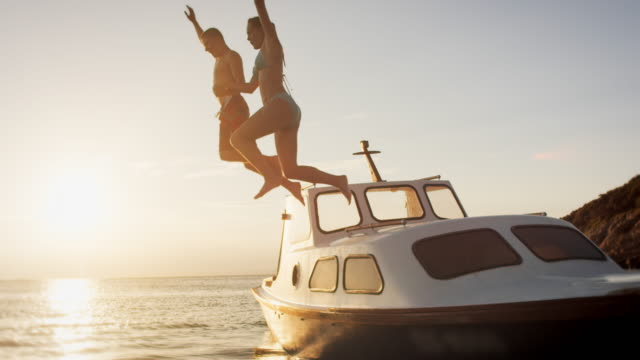 slo mo couple jumping off a boat in sunset - vacanze video stock e b–roll