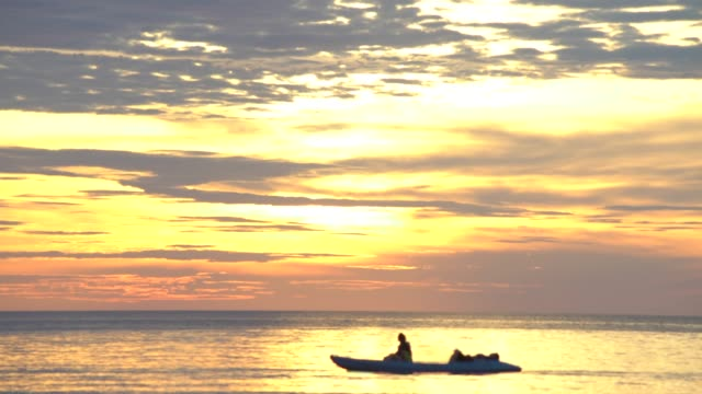 couple Kayaking in  the sea with bright gold sunset colour sky background cinemagraph 4K loopable