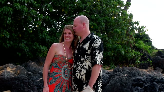 Couple kiss and laugh on beach in Hawaii slow motion video