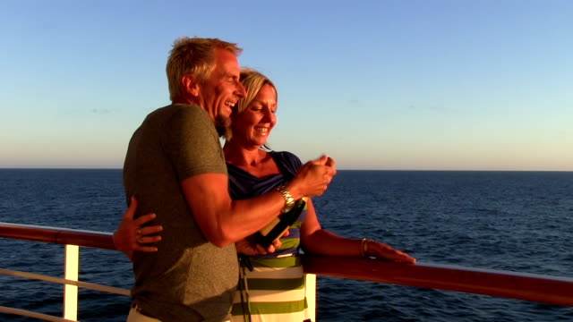 Couple kiss open champagne on cruise during sunset. video