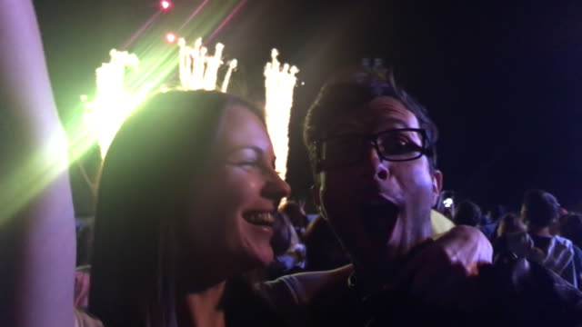 couple kissing at a night concert during fireworks - brunette woman eyeglasses kiss man video stock e b–roll