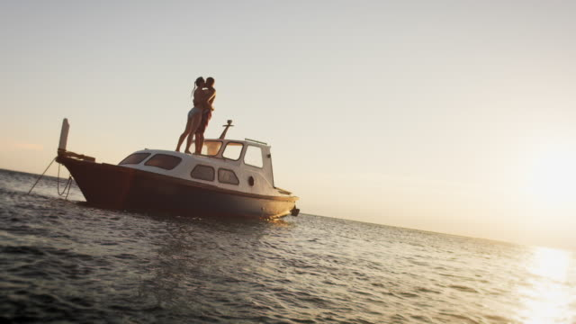 SLO MO Couple kissing on the boat at sunset video