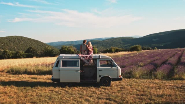 couple kissing on van against idyllic landscape - vacanze video stock e b–roll