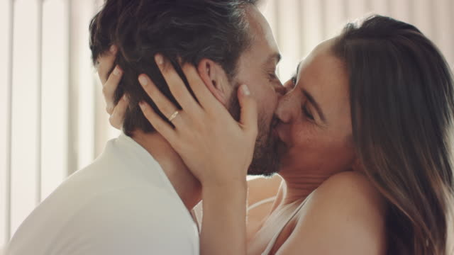 Couple kissing Couple sitting on bed kissing each other kissing stock videos & royalty-free footage