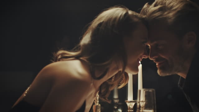Couple kissing Couple having a romantic candle light dinner. They kissing each other.   date night romance stock videos & royalty-free footage