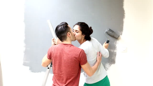 Couple kissing while painting wall with paint roller video